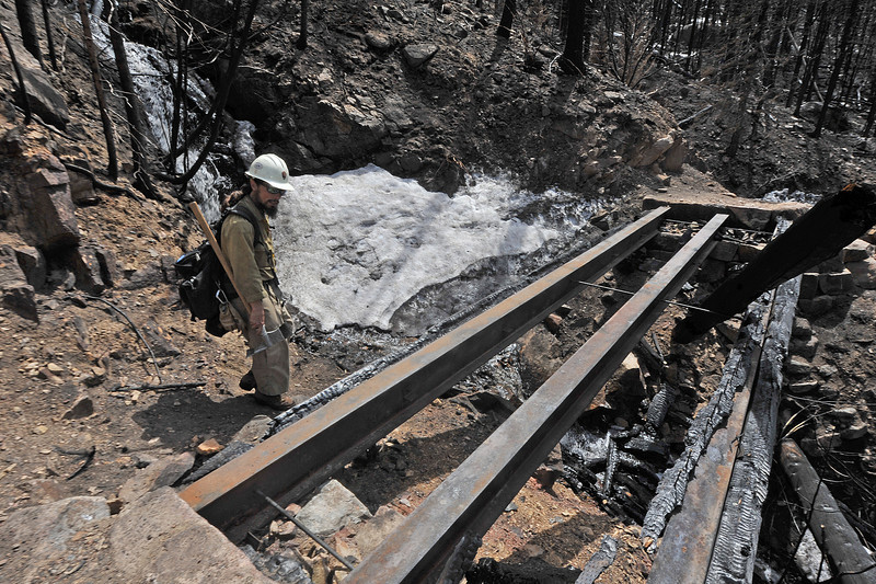Alpine Hotshot fire captain Mark Mendonca looks at the burnt remains of a bridge along the Cub Lake Trails on Monday. A few bridges and one provate inholding were lost in the Fern Lake Fire.