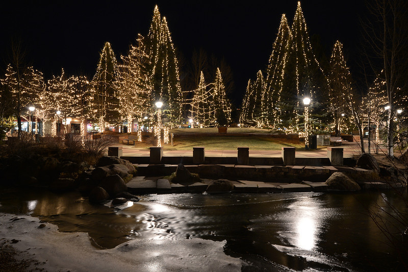 Lights on Riverside Plaza reflect on the Fall River on Saturday night. The festive plaza attracts visitors even in the chill of the dark hours.