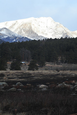 The snowy face of Mount Ypsilon stands above the charred, dry grass of Moraine Park on Thursday morning. More snow may fall on the peak and on Estes Park this weekend.