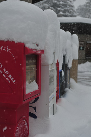 Snow piled high on newspaper boxes create peaks on Monday.