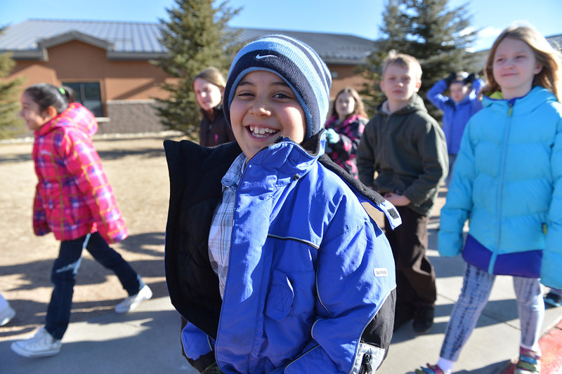 Eight-year-old Miguel Gonzales zips up his jacket on the way to the elementary school playground on Thursday. Winds were, again, more of an issue than the temperature, as the had warmed to the mid 30s by 9:30 a.m.