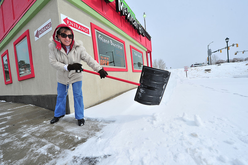 Carolyn McEndaffer scoops about an inch of snow off the front sidewalk at Peppers Mexican Grill on Thursday. New snow tangled traffic on the Front Range and Plains, but was light and very welcome in Estes Park.