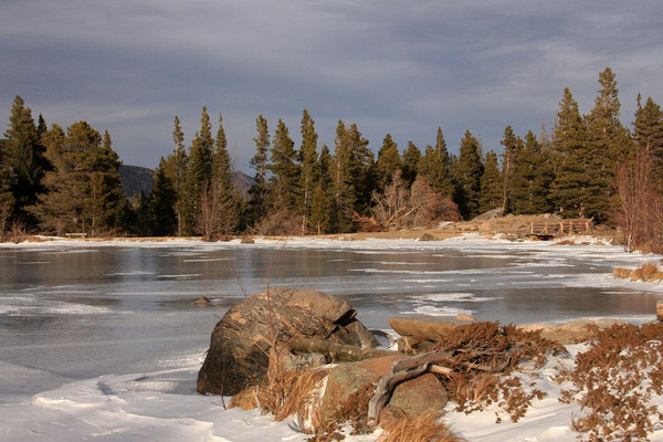 Ice covers Sprague Lake in Rocky Mountain National Park under an overcast mid-December afternoon sky.