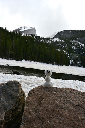A visitor showed an artistic vent in constructing this diminuative snowman on the shores of Bear Lake in Rocky Mountain National Park. Hallett Peak can be seen in the background with storm clouds rolling in. The Bear Lake area saw very light snowfall late Sunday afternoon, about two hours before sundown.