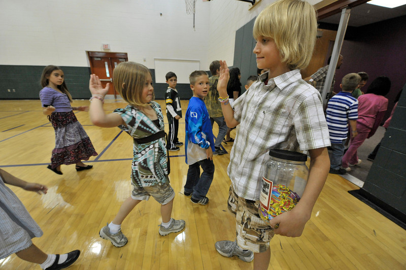 Photo by Walt Hester<br /> Shane Wens, 10, slaps hands with students exiting the annual ABC fund raiser assembly on Wednesday. Estes Park is regularly in the top schools for fund raising per student.