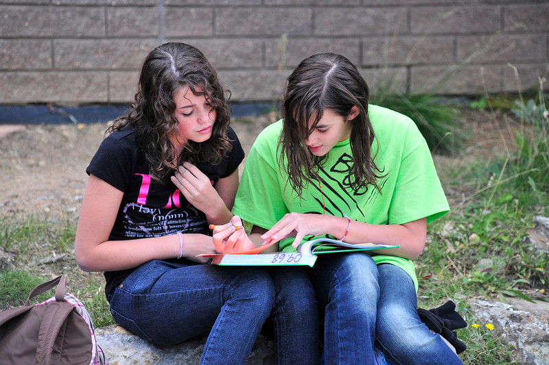 Photo by Walt Hester<br /> Josephine Christianson, left, and Courtney Schlarbaum, both 12, study after their swim practice at the Aquatic Center on Tuesday.