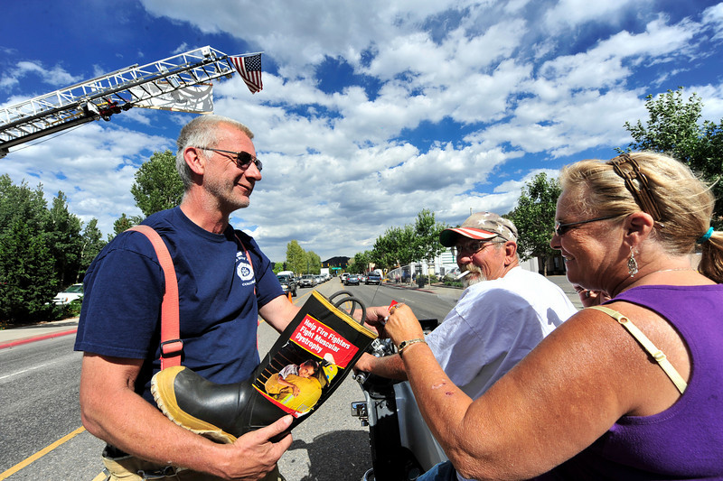 Photo by Walt Hester<br /> Estes Park volunteer firefighter Bruce Walters collects donation for the Muscular Dystrophy Foundation along Elkhorn Avenue on Saturday. Fill the Boot is an annual event in Estes Park and in many communities around the nation.