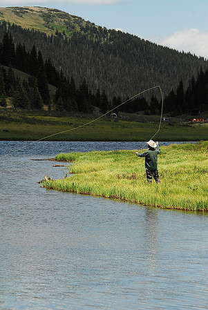 Photo by Walt Hester<br /> A fly fisherman casts into Poudre Lake. The lake, which sits on Milner Pass, is the source of the Cache La Poudre River, which flows into the Platte River and eventually the Gulf of Mexico, while water from the opposite side of the parking lot flows into the Colorado River toward the Sea of Cortez and the Pacific.