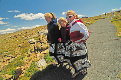 Photo by Walt Hester Nebraska natives, from left, Chelsea Entz, 17, Kelli Bauer, 15, and Kara Ostrand, also 15, skip down the Tundra Communities Trail while covering themselves in a quilt. The cool tundra and stiff winds made for an uncomfortable visit to the top of Trail Ridge Road.