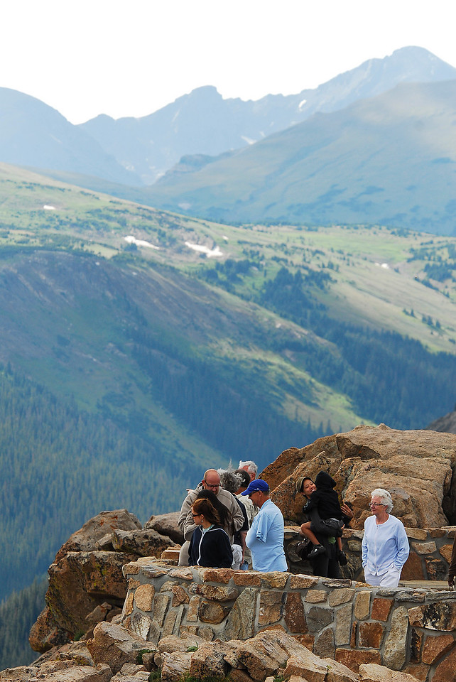 Photo by Walt Hester<br /> Visitors peer over the precipice at the Forest Canyon Overlook. Visitors can see Longs Peak, the Continental Divide and the park's western border, the Never Summer Range from the view point.