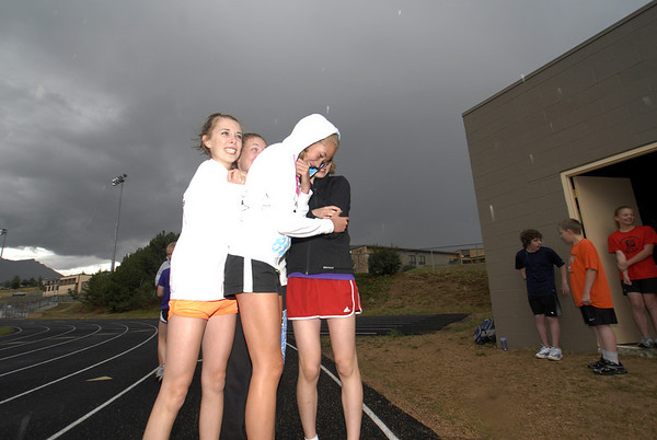 Photo by Walt Hester<br /> High school cross country runners huddle to stay warm as rain begins to fall at Bobcat Stadium on Wednesday. While some sports head inside when the skies open up, runners keep running.