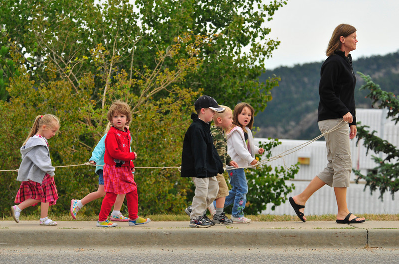 Photo by Walt Hester<br /> Sue Strom leads a group of pre-school children on a walk along South St. Vrain Avenue on Wednesday. The rope, along with more adult helpers who brought up the rear of the group, helped the children stay in a line.