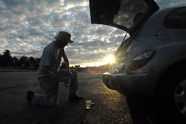 "Photo by Walt Heter<br /> Plein Air painter Bob Thoren watches the sunrise while mixing paint thinner in the National Park Village parking lot on Wednesday. The Plein Air show hits its stride this weekend with the annual ""Quick Draw"" and auction at Riverside Plaza on Saturday."
