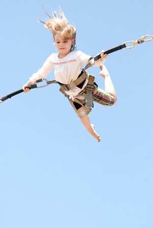 Photo by Walt Hester<br /> Katy Angerame, 4, of Wilton, Conn., hangs high above Estes Park from bungee cords on Friday, Aug. 21. The local amusements parks are only open on weekends and school has begun in Estes Park.