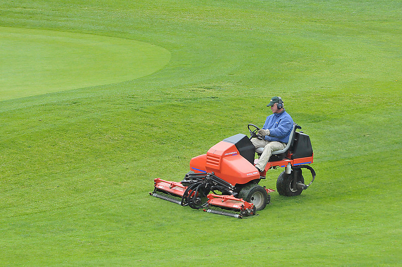 Photo by Walt Hester<br /> A recreation and parks worker trims the vibrant grass of he Lake Estes 9-hole golf course on Thursday. The cool and wet weather has made the greens greener and the rough rougher on the two municipal courses.