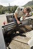 Photo by Walt Hester<br /> Division of Wildlife officer Rick Spowart examines a euthanized bear on Friday. The 4-year-old female had become habituated to breaking in to homes, as well as bird feeders and garbage bins.