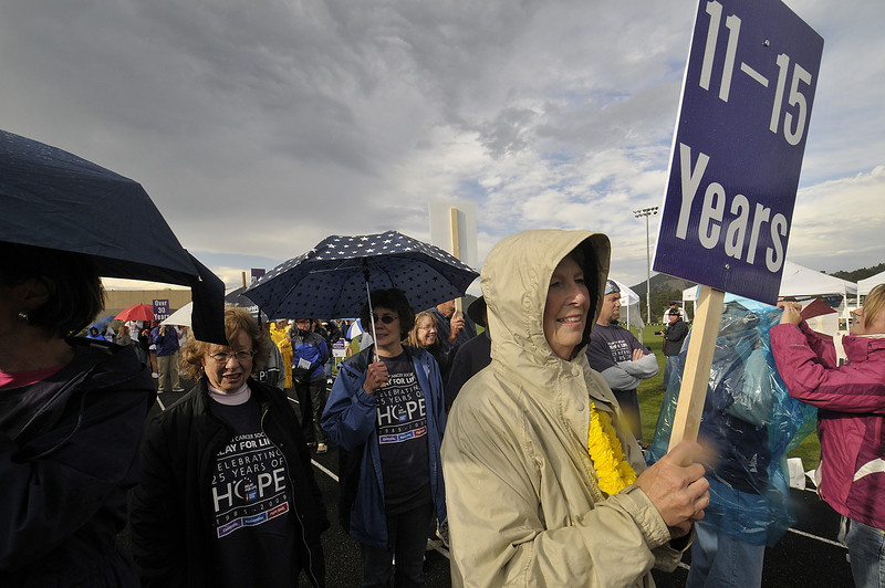 Photo by Walt Hester<br /> Long-term cancer survivor Joan Allen of Estes Park leads her group during the Survivors' Lap that kicks off the Relay for Life Friday evening. While rain showers delayed the start and revisited the event, they could not dampen the spirits of the participants.