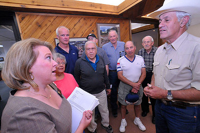 Town Clerk Jackie Williamson receives a stack of petitions from Bill Van Horn as a group of petition supporters looks on. The petition asks the town of Estes Park to abolish EPURA. Photo by Walt Hester.