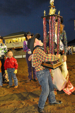 Andrew Stevens of Boulder holds up a trophy as tall as himself after the Mutton Busting event at the Rooftop Rodeo on Tuesday. Photo by Walt Hester.