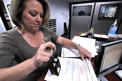 Town Clerk Jackie Williamson marks petitions handed in on Wednesday urging the town to end EPURA. Photo by Walt Hester.
