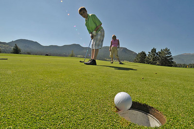 Will Casey, 15, sinks a putt on the fifth hole of the Estes Park public 18-hole course. Photo by Walt Hester