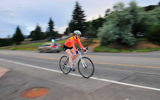 Photo by Walt Hester<br /> A cyclist streaks down S. St. Vrain Avenue on Monday as night begins to fall over Estes Park.