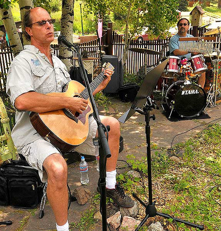 Photo by Walt Hester<br /> Musicians Dave Gandol, left, and Steve Jackson perform for visitors to Glen Haven on Saturday. While the musicians were playing at a local shop, they could be heard all down the main street.