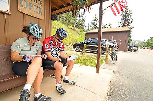 "Photo by Walt Hester<br /> Stephany Struble and Brian Bergevin, both of Denver, rest and read in Glen Haven before tackling the infamous ""Switchbacks"" on Devils Gulch Road on Saturday. With beautiful scenery and a challanging climb, cyclists flock to Glen Haven, especially in the warm summer months."