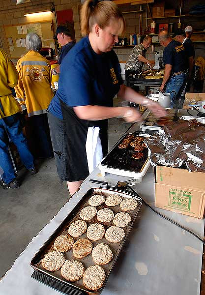 Photo by Walt Hester<br /> Tricia Kob cooks up sausage at this Saturday's pancake breakfast. The fire department's breakfast is a tradition in Glen Haven, with several second-generation volunteers, like Kob, who's father hhad served as a firefighter and a breakfast cook.