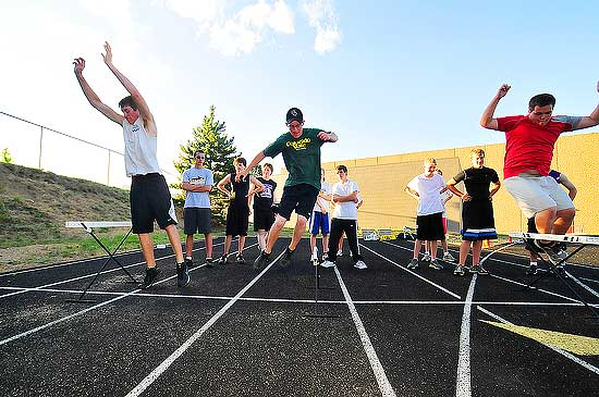 """Photo by Walt Hester<br /> Luke VanHorn, Jordan Coleson and Blake Hinsen jump over low herdles during """"Speed Camp"""" at Bobcat Stadium on Thursday. The exercise trains athletes to jump quickly and lightly to develope foot speed."""