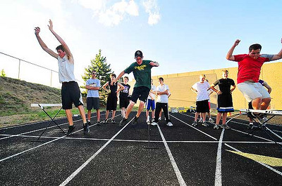 "Photo by Walt Hester<br /> Luke VanHorn, Jordan Coleson and Blake Hinsen jump over low herdles during ""Speed Camp"" at Bobcat Stadium on Thursday. The exercise trains athletes to jump quickly and lightly to develope foot speed."