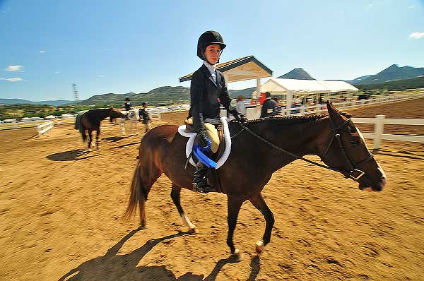 Andra Sakson, 12, of Carbondale heds back to the stables after nabbing the blue ribbing in Pony Equitation on Wednesday morning. The event is horsemanship for younger girls.