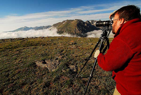 Photo by Walt Hester<br /> Artist-in-Resident Carl Johnson of Anchorage, Alaska photographs the conjunction of Longs Peak, low clouds and bull elk from near Forest Canyon Overlook on Wednesday morning. The low, rainy clouds over Estes Park gave way to sunny, blue skys at 12,000 feet.