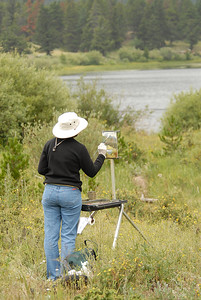 Photo by Walt Hester Carol Andreyev, a summer resident of Estes Park, paints at Lily Lake on Wednesday.