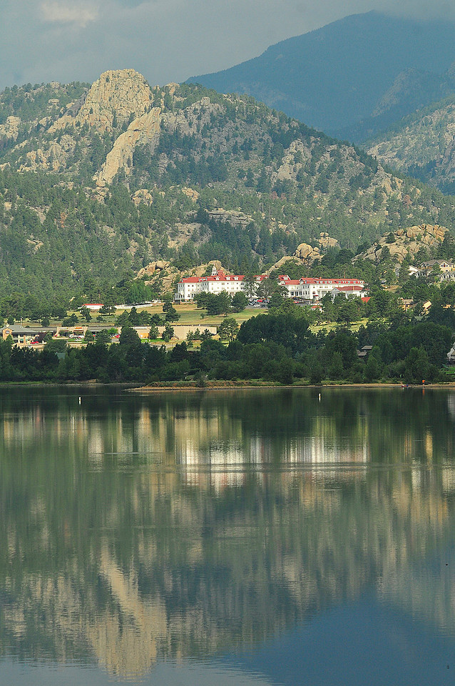 Photo by Walt Hester<br /> Sunshine peeks through to illuminate the Stanley Hotel and reflect off of Lake Estes on Wednesday morning. Rain and small hail returned to the area later in the afternoon.