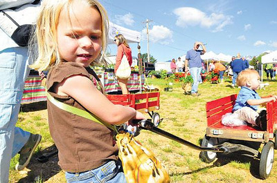 Farmers market rolls in Claire Reed, 3, pulls her 16-month-old brother, James, through the season-opening farmers market at the Stanley Fairgrounds on Thursday. The market, offering flowers, baked goods, local meat and much more, will be at the fairgrounds every Thursday through the end of September. Photo by Walt Hester