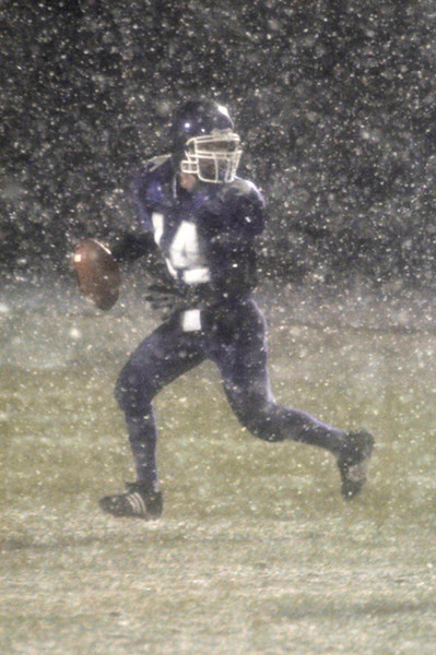 Photo by Walt Hester<br /> Estes Park's Caleb Hightower rolls out into challenging visibility during Friday's tilt with Valley High School. Heavy snow hindered the Bobcats' passing game.