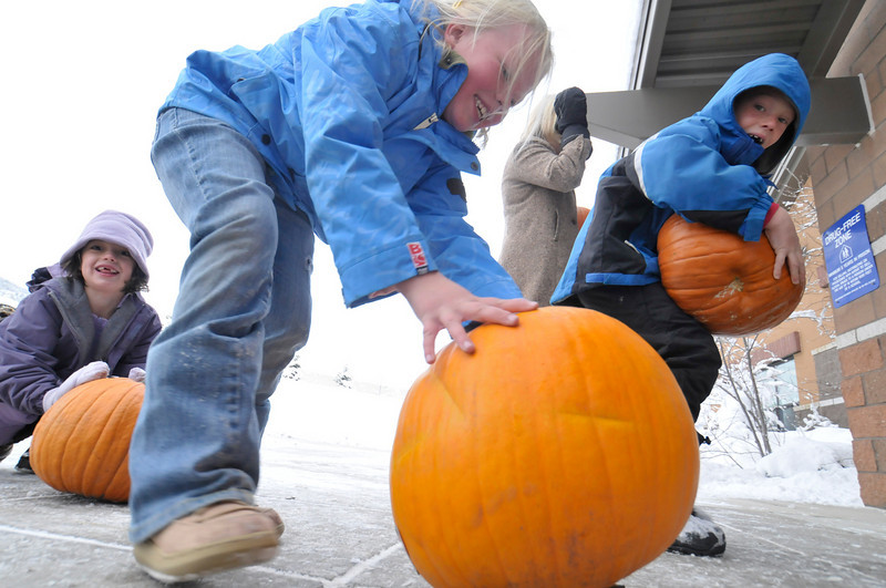 Photo by Walt Hester<br /> Ellie Bergsten, 6, center, rolls her pumpkin back into the Estes Park Elementary School on Thursday. The Estes Park Noon Rotary club, once again, gave away pumpkins to the students, with the help of Safeway, who donated more than $1,000 worth of the seasonal squash.