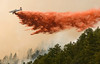 Photo by Walt Hester<br /> A single engine slurry bomber drops the red retardant on the Dunraven Fire about three miles west of Glen Haven on Tuesday. By Wednesday afternoon, firefighters had the 46-acre fire about 60 percent contained.