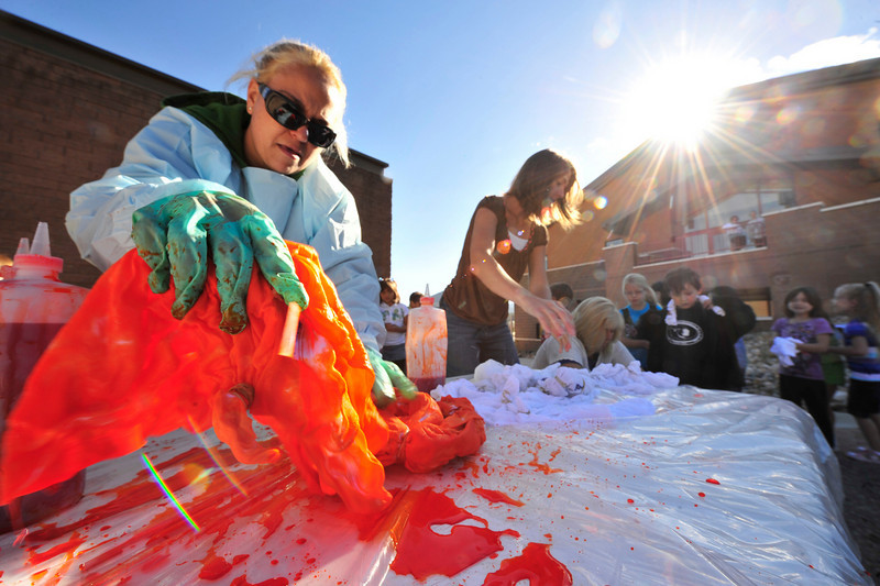 Photo by Walt Hester<br /> Lisa Peters of the elementary school's Parent-Teacher Organization dips t-shirts into bright orange dye at the elementary school on Tuesday. Each school got different colors for their tie dye shirts, with the first grade getting orange.