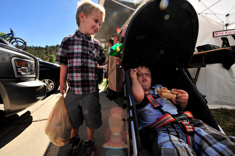 Photo by Walt Hester<br /> Noah Issenhuth, left, 4, and two-year-old brother, Lucas, both of Golden, enjoy a day at at the Fine Arts Guild Fine Art Fair in Bond Park on Sunday. The annual event invites artists from far and wide to spend a fall weekend in Estes Park.