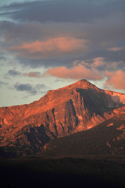 Photo by Walt Hester<br /> Day breaks on Hallett Peak and the clouds over the peak on Friday.