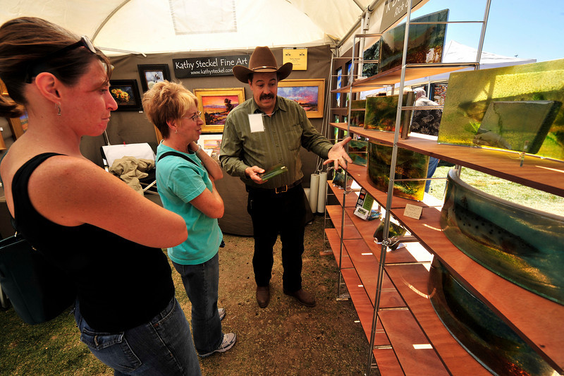 Photo by Walt Hester<br /> Artist Rick Steckel of Crawford, Colo. explains his process to Audra and Becky Lewthwaite of Denver at Sunday's Fine Art Fair in Bond Park. The fair is an annual event put on by the Fine Arts Guild of the Rockies.