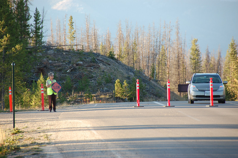 A volunteer directs traffic early Saturday evening near the Kawuneeche Visitor Center on the park's west side. Official closed the road between the visitor center and Milner Pass after the Onahu Fire broke out Saturday afternoon.