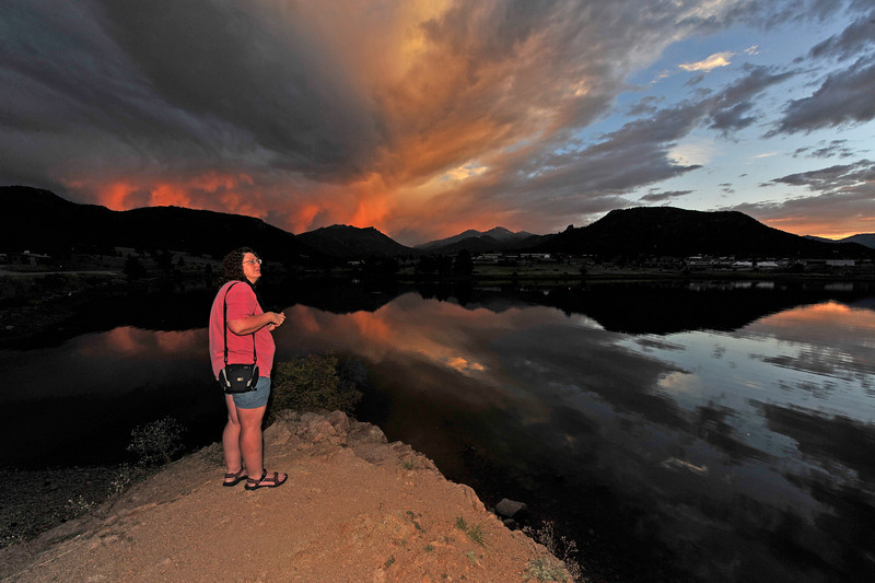 01EP StndAln Sunset.jpg Photo by Walt Hester<br /> Regina Palmer of Littleton stands by Lake Estes to photograph Friday's sunset. Changing weather patterns create beautiful skys at the start and end of the day.