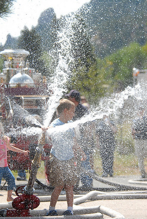 Photo by Walt Hester<br /> Lucas Russell, 7, of Estes Park plays in the stream created by a 1901 steam pumper before a wetting ceremony for the Estes Park Volunteer Fire Department's newest truck on Saturday. The public was invited for tours of the fire station, free hotdogs and the wetdown of the new truck.