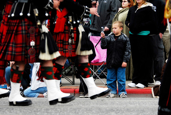 A boy takes a cell phone snap shot of the passing 1st Battalion Scots Guards Pipes and Drums during Saturday's annual Longs Peak Scottish-Irish Highland Festival Parade. The festival attracts athlete, musicians and visitors from all over the world to Estes Park.