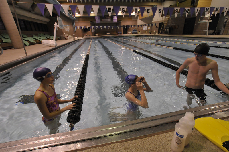 Photo by Walt Hester<br /> Middle school swimmers Holly Holmes, 12, Emma Reins, 13, and Forrest Beesley, 14, sneek in some pool time before school on Tuesday. The middle school swimmers begin their season tonight against Erwin and Ft. Lupton middle schools.