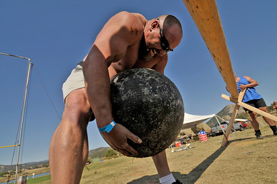 Photo by Walt Hester Elizabeth strongman Rob Lewis hefts a 350-pound stone over a 3-foot-high caber to win Friday's strongman competition. This was the first time a strogman competition has been part of the Highland Athletics event at the festival.