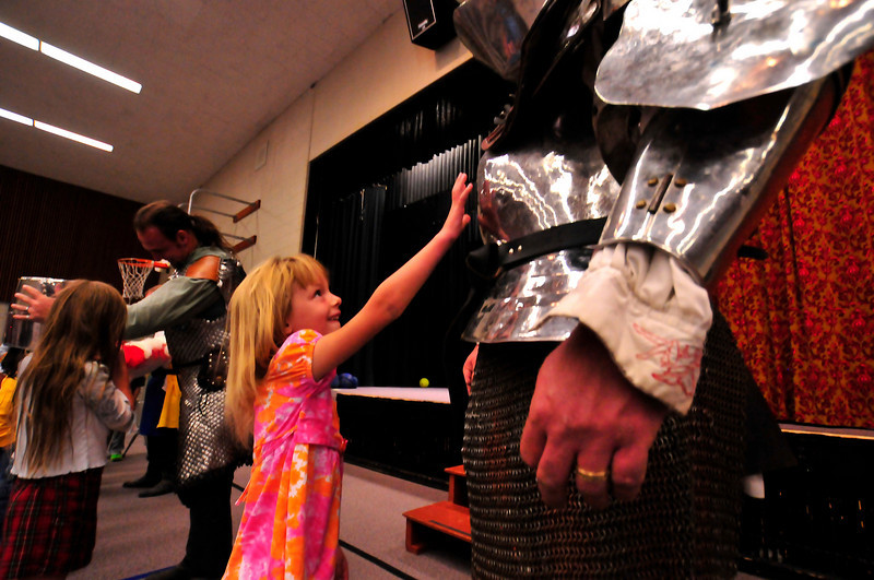 Photo by Walt Hester<br /> Kaitlynn Kennedy, 6, reaches out to touch the armor worn by world champion jouster Shane Adams at the old elementary school gym on Thursday. Adams was in Estes Park for the Longs Peak Scottish-Irish Highlands Festival this past weekend.